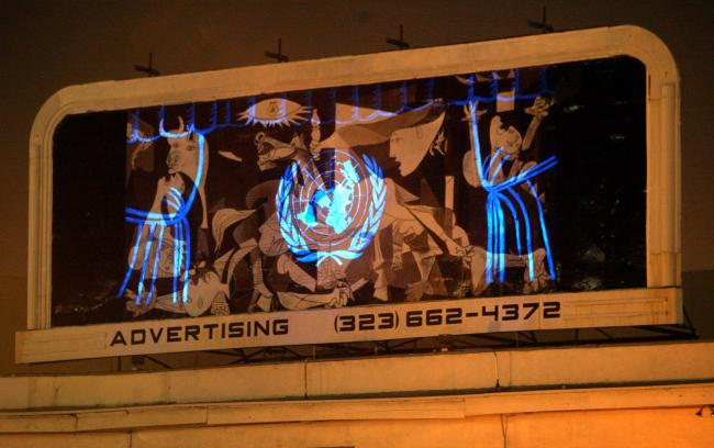 Réplica de Guernica con el logotipo de la ONU proyectado en la intersección de Hollywood and Sunset Boulevard