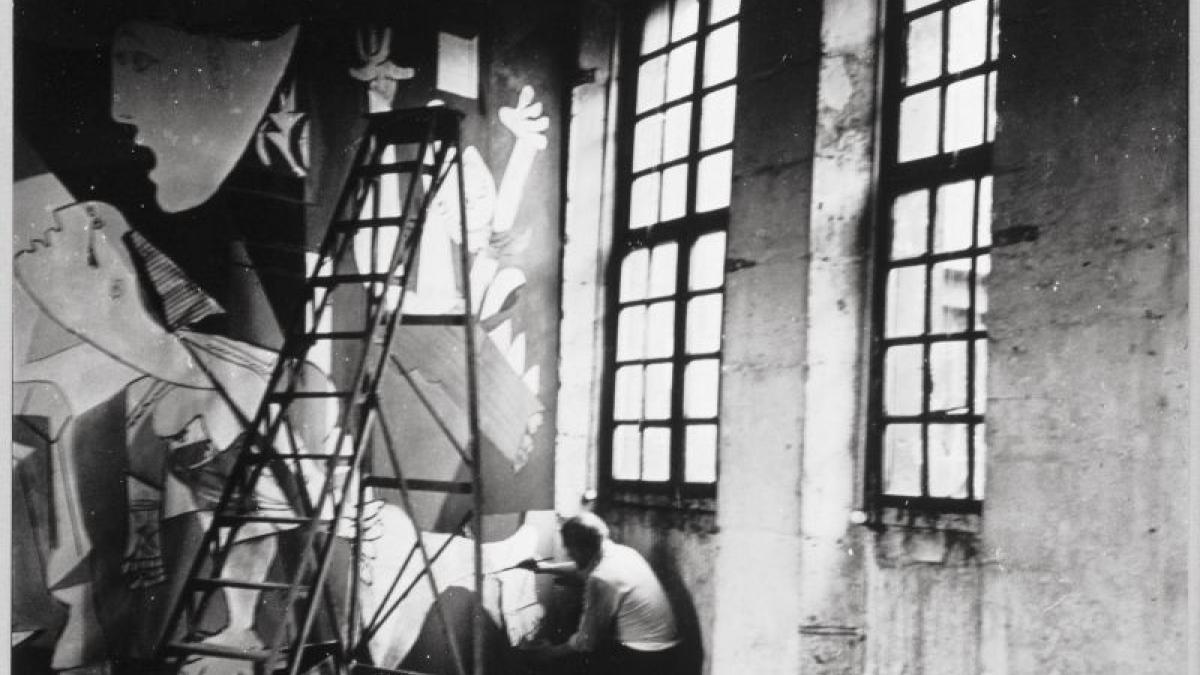 Picasso fotografiado por Dora Maar sentado en el suelo de su estudio trabajando en Guernica