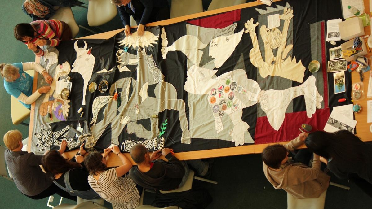 A collective banner bearing the image of Guernica