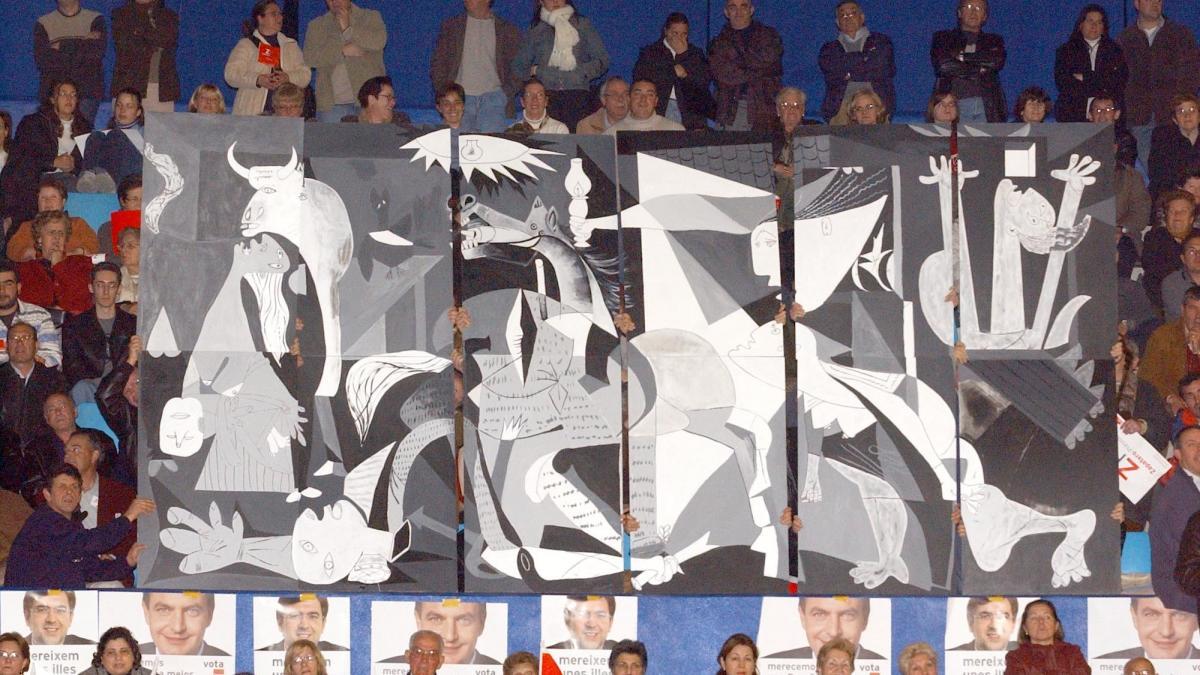 Simpatizantes socialistas izan una pancarta de Guernica durante el mítin del candidato José Luis Rodríguez Zapatero