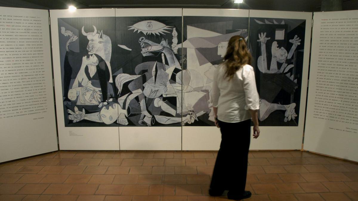 Una mujer contempla uno de los paneles ilustrativos de la exposición Pablo Picasso, Guernica. Historia de un cuadro