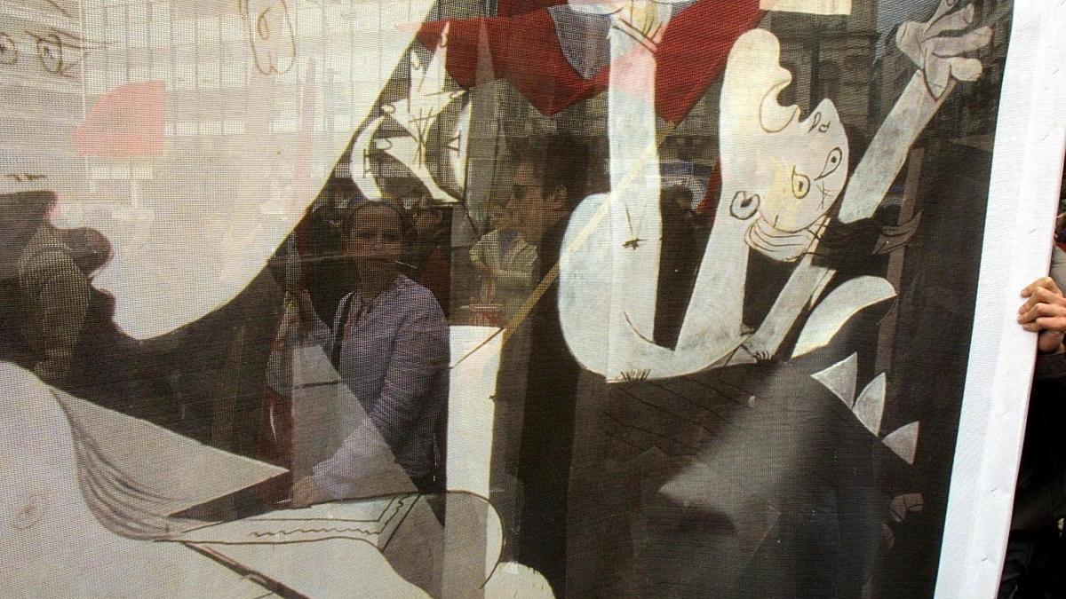 Manifestantes vistos a través de una pancarta con la imagen de Guernica en una protesta contra la invasión de Irak