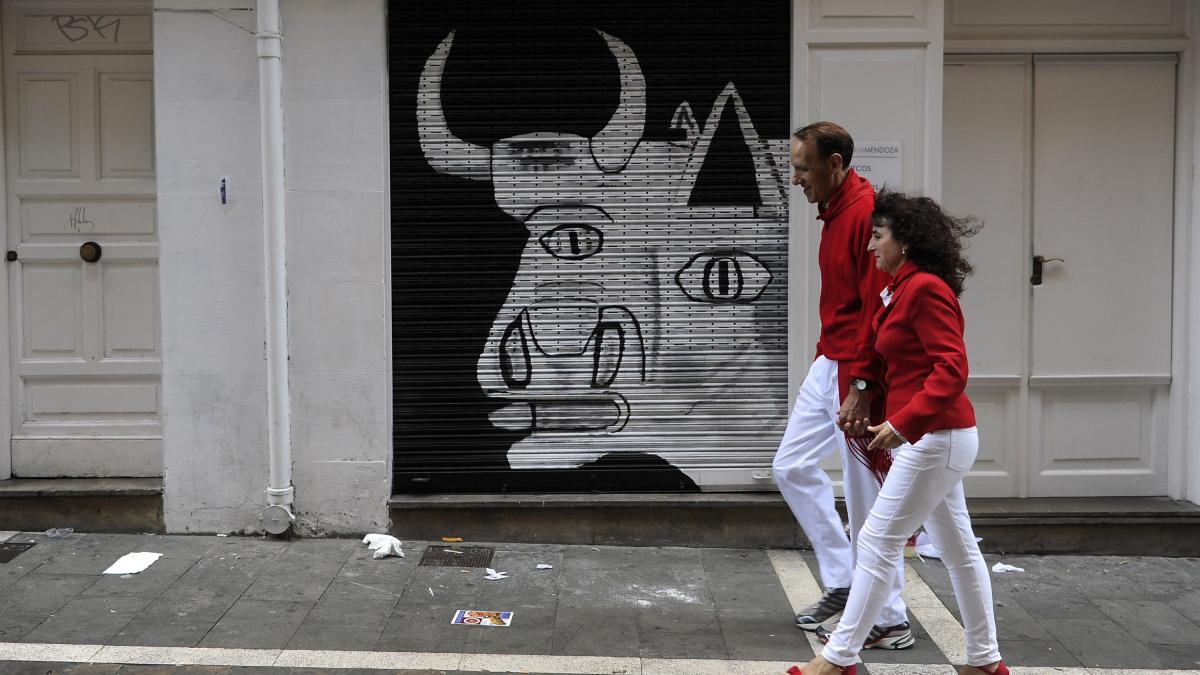 Dos personas caminan frente a una reproducción de un fragmento de Guernica durante las fiestas de San Fermín