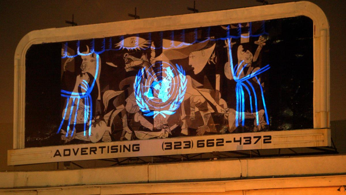 A replica of Guernica with the UN logo projected at the intersection of Hollywood and Sunset Boulevard